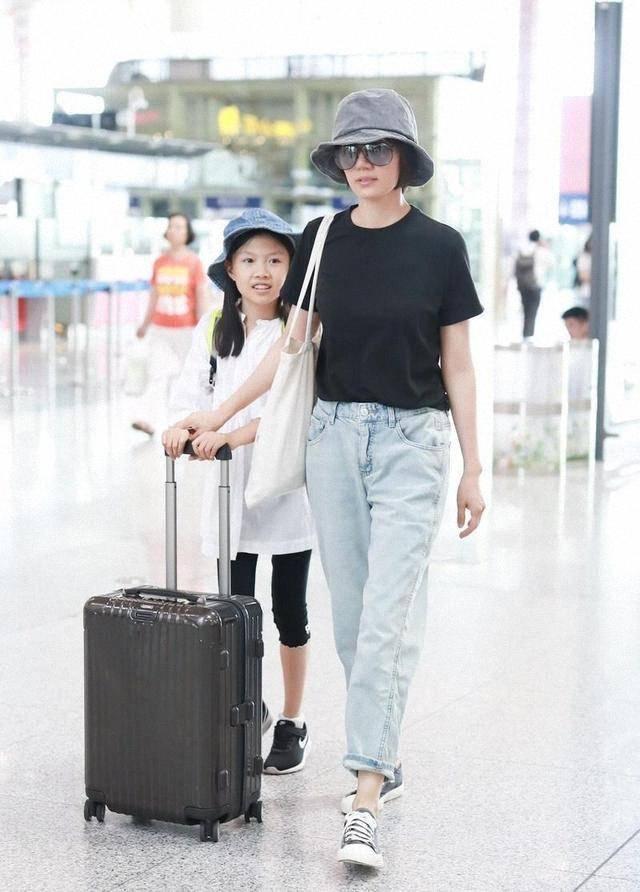 袁泉带女儿走机场,穿牛仔裤配帆布鞋接地气,气质依旧藏不住