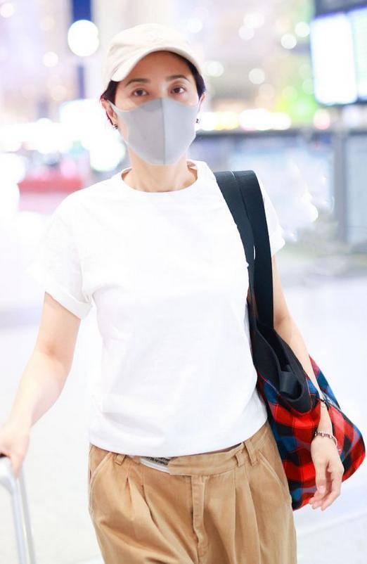 原创             曾黎素颜走机场,穿白T恤搭束脚裤简单又随性,红色挎包土味十足