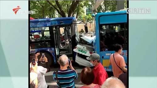 广州的一辆小车被两辆公交车夹在一个三