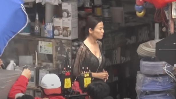 50岁宣萱在片场拍戏,穿黑色网状丝袜配红色高跟鞋,表情显尴尬